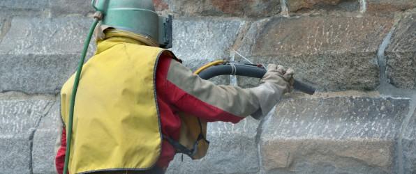 man in beschermd pak bezig met gevelreiniging van een gebouw door middel van zandstralen
