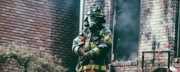 Foto van brandweerman voor uitgebrand pand. Brand voorkomen is niet gelukt.